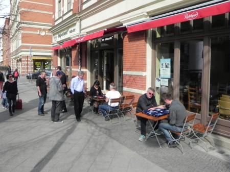 Straßenszene in Berlin: Backgammon bei sonnigem Wetter vor dem Lokal. Im Vordergrund Michael und Sokrates (mit Sonnenbrille), dahinter Gerhard und Iris mit Kiebitzen