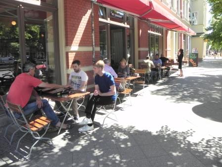 Sommerbackgammon: Stefan Blanke zieht, Faruk Kocaer schaut zu, Malte Quiter kiebitzt. Dahinter Sabine und Kurt