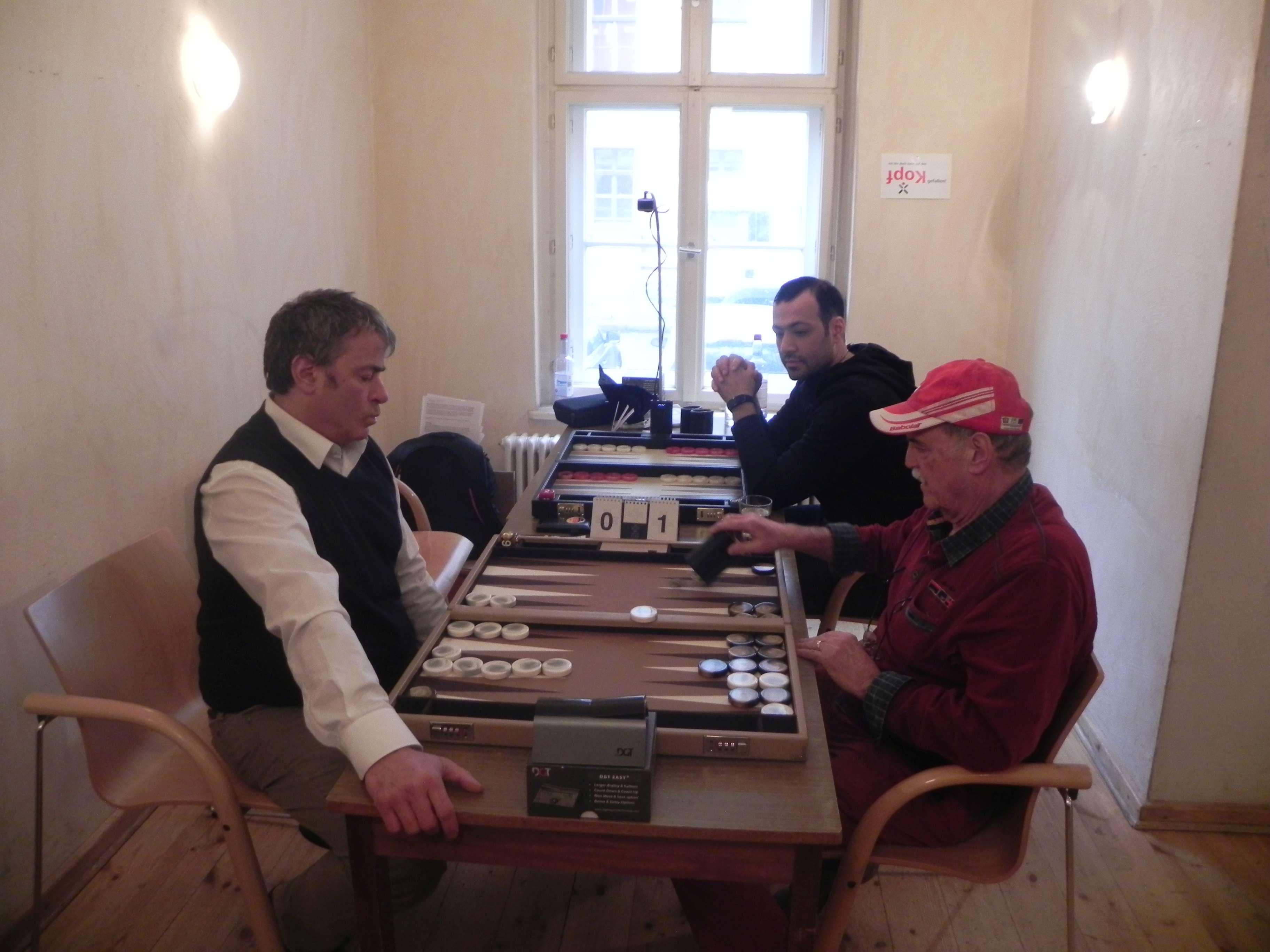 Andreas Kohlschmidt (li) und Carlo Petkovsek. Dahinter wartet Amir Golshani auf seinen Gegner, den Turnierleiter, der als Paparazzo noch eine Runde durchs Spiellokal dreht